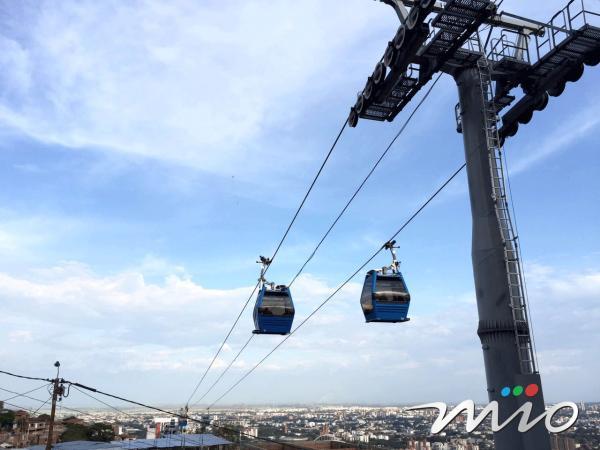 Vista desde tierra de dos carrozas del Mio Cable pasando por la estación Lleras